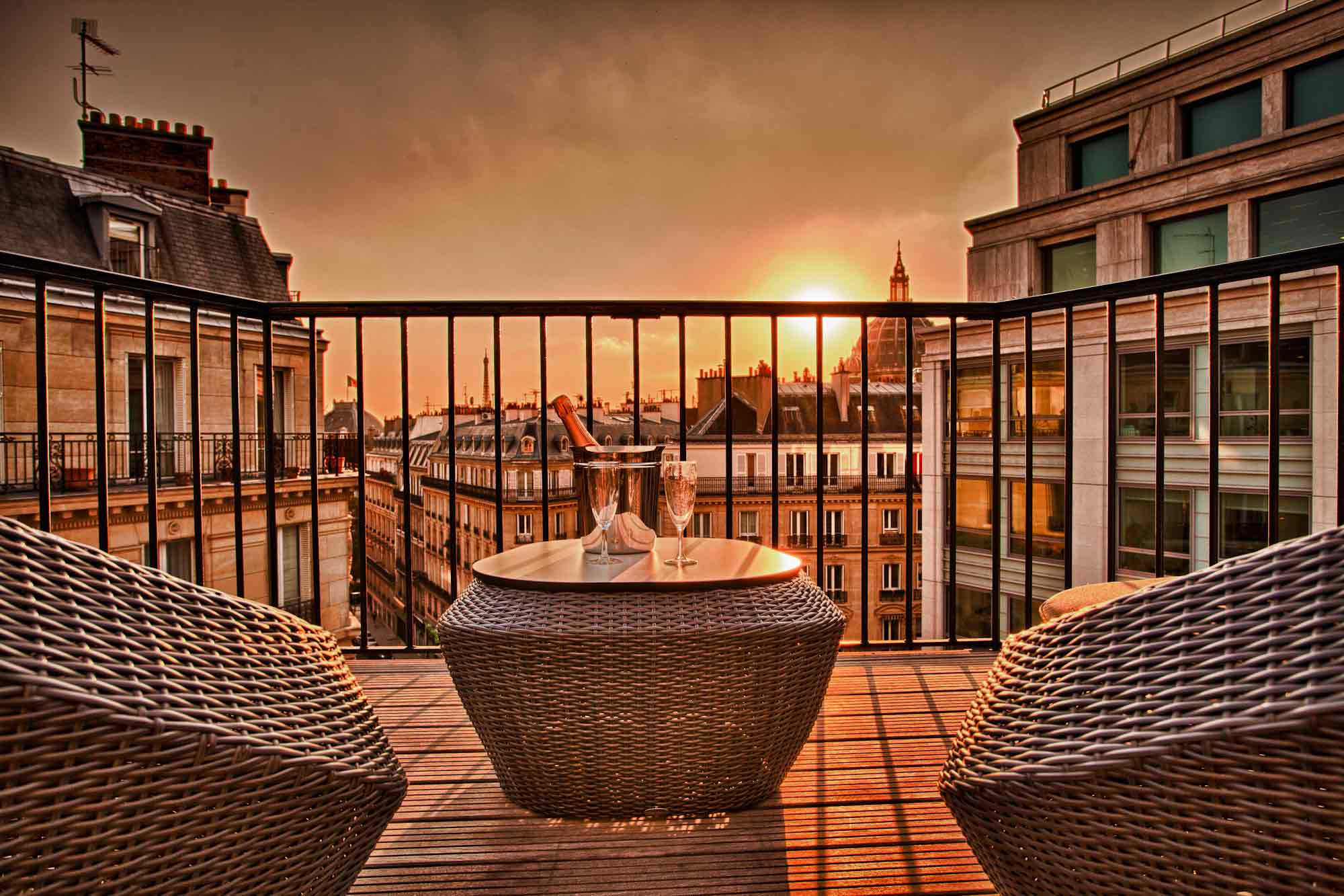 Terrasse parisienne avec soleil couchant, équipée de fauteuils et coupes de champagne