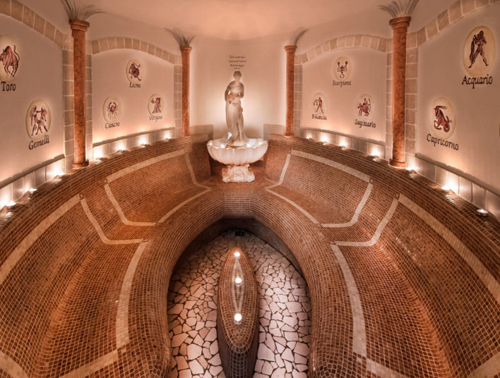 Salle de spa italien avec murs carrelés de couleur ocre avec les signes du zodiaque sur les murs
