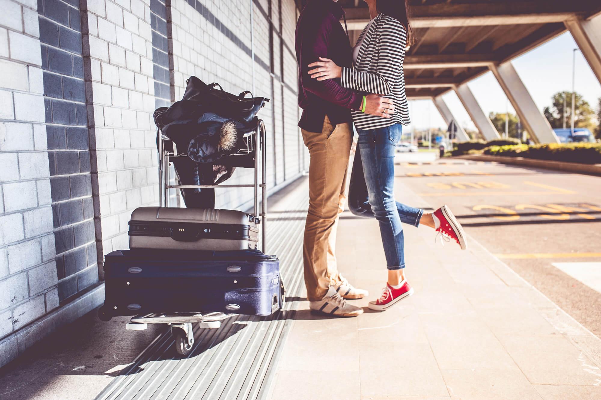 Couple avec chariot rempli de valises en train de s'embrasser sur le quai de la gare avant de partir pour un voyage surprise