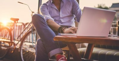 Homme en chemise assis le soir dehors en train d'organiser un voyage surprise sur son ordinateur