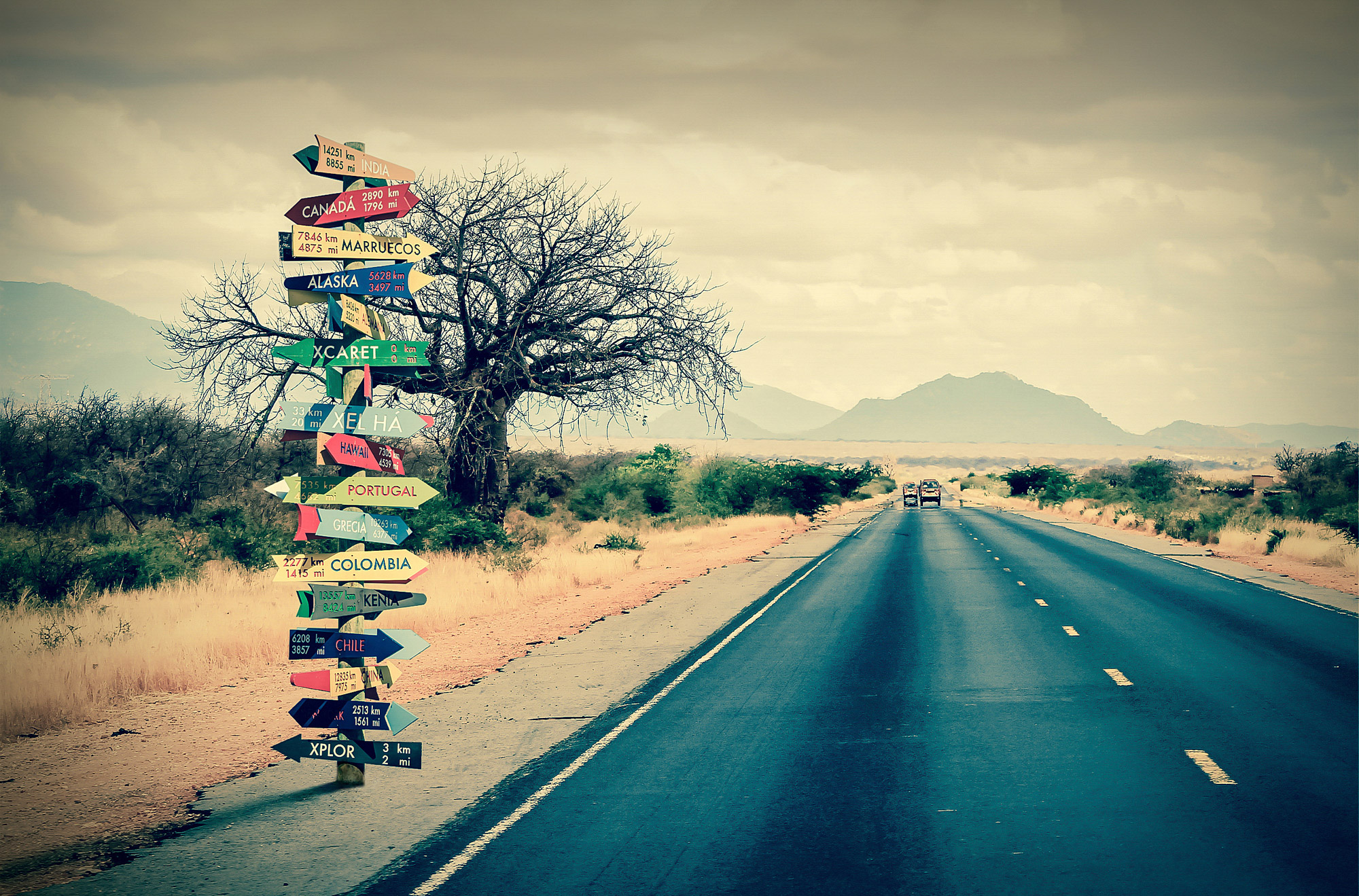 Route principale avec des paneaux d'indication pour partir en vacances partout dans le monde