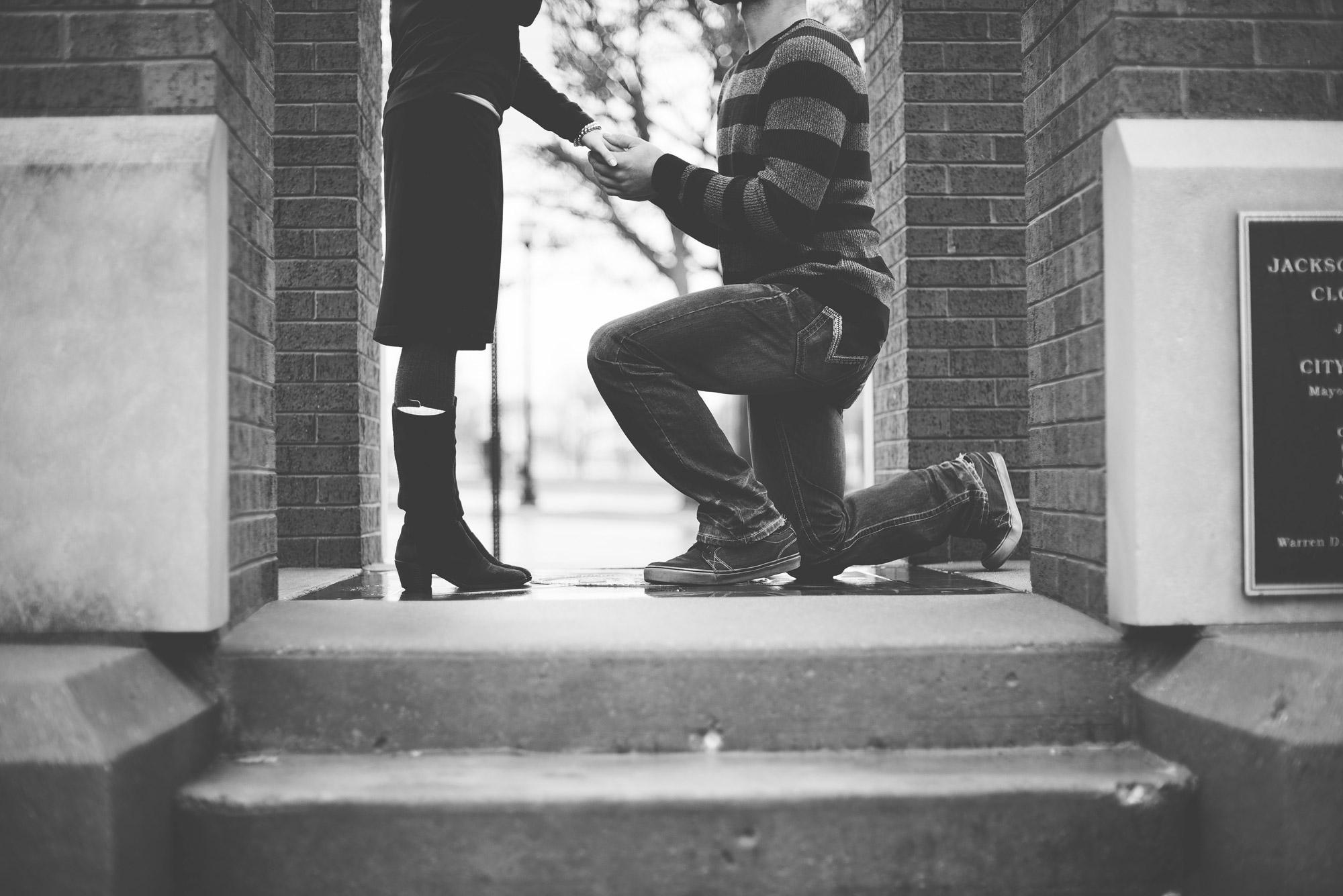 Couple en pleine demande en mariage originale, avec le fiancé agenouillé dans la rue