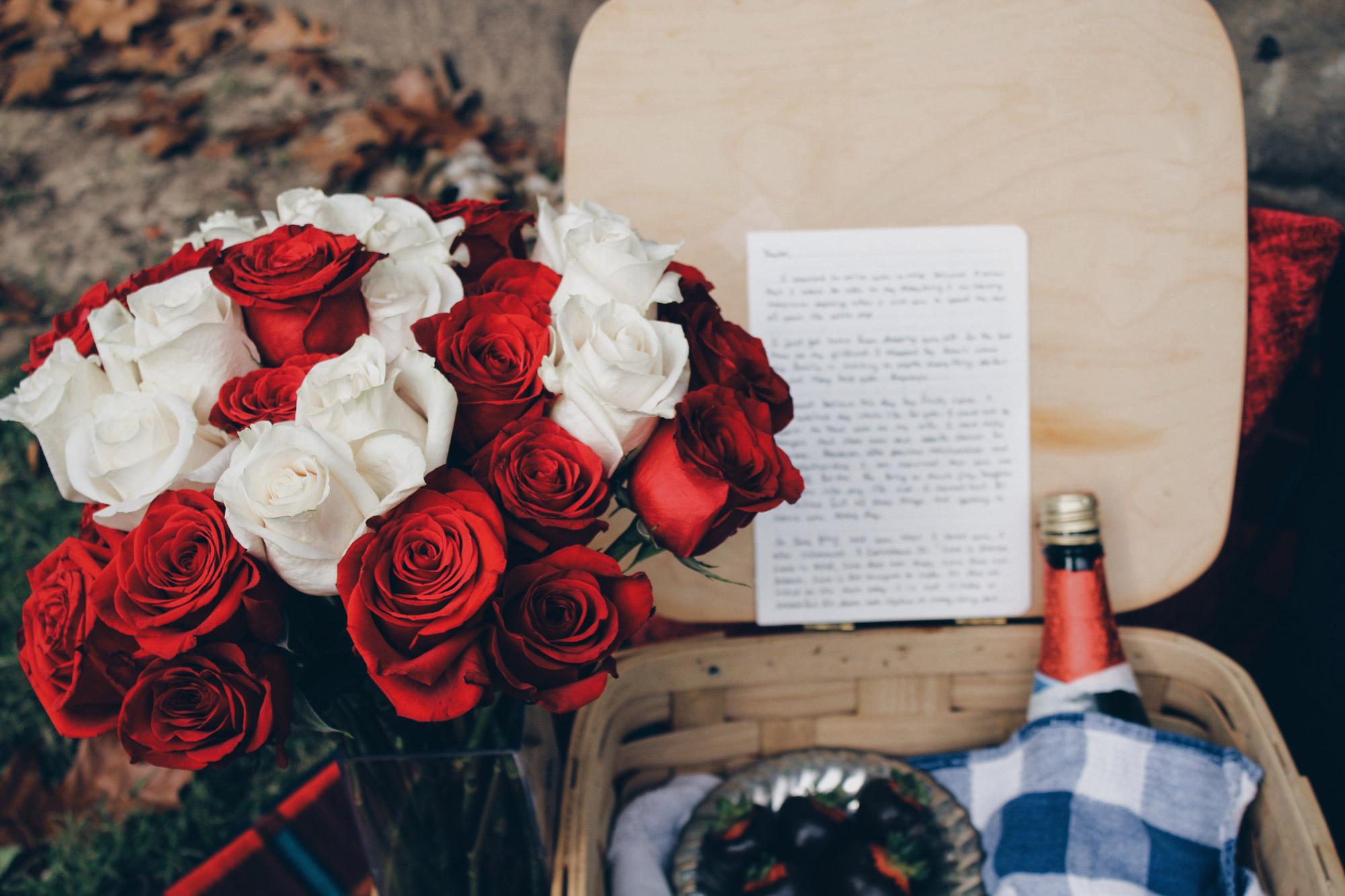 Panier de pique-nique romantique avec un bouquet de roses et une bouteille de vin