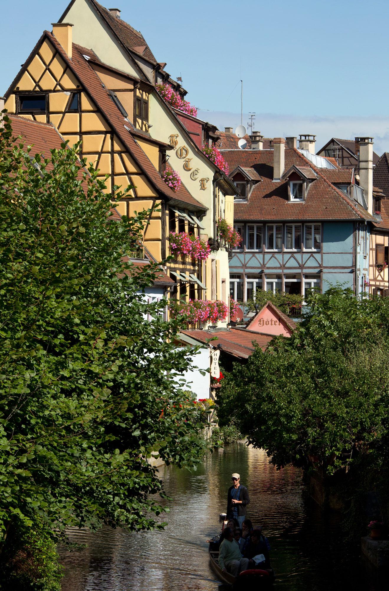 Personnes assises dans une barque en promenade sur les canaux d'Alsace