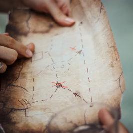 Mains posées sur une carte au trésor de type parchemin à l'ancienne