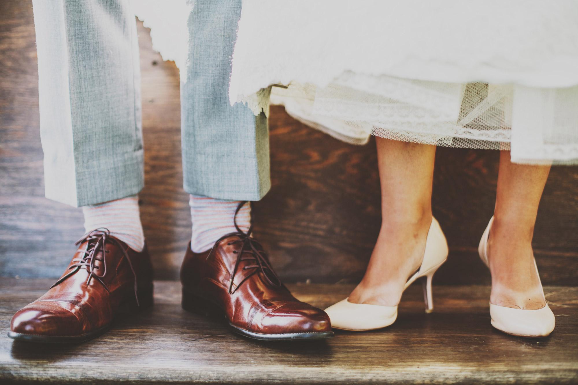 Gros plans sur des pieds d'homme et de femme semblant appartenir à des mariés