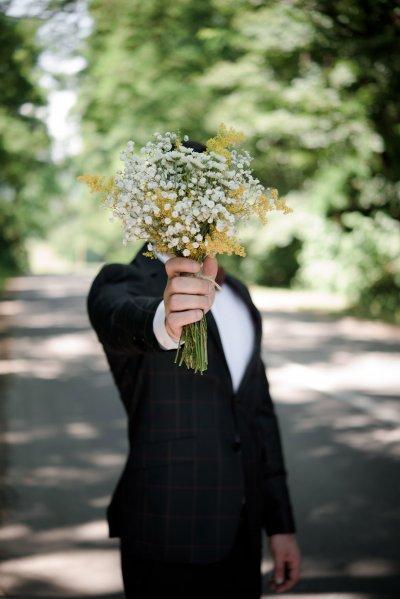 Homme tendant un bouquet de fleurs pour une demande en mariage originale