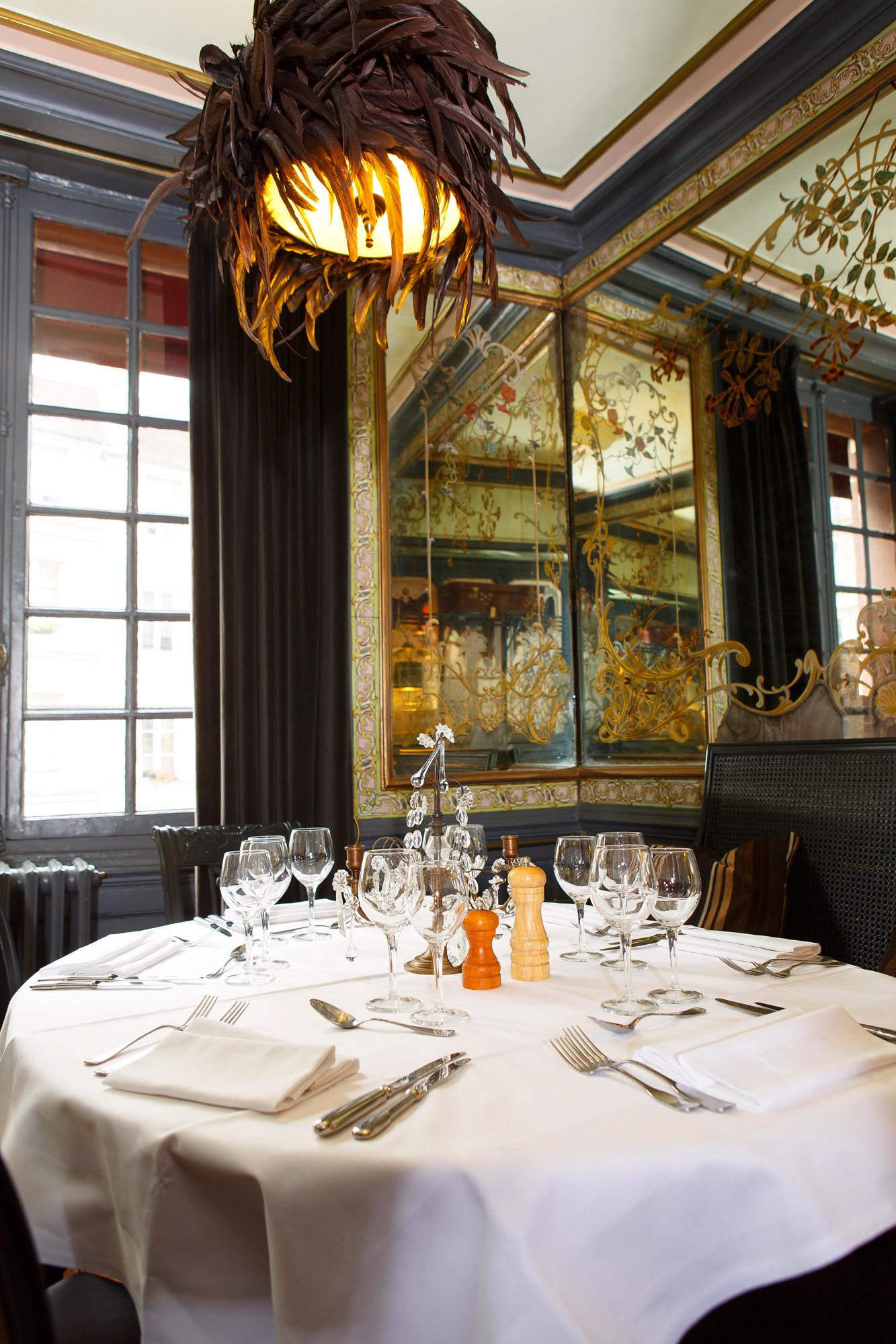 Table dressée avec miroir sur les côtés et lustre à plumes dans le restaurant Le Pharamond à Paris