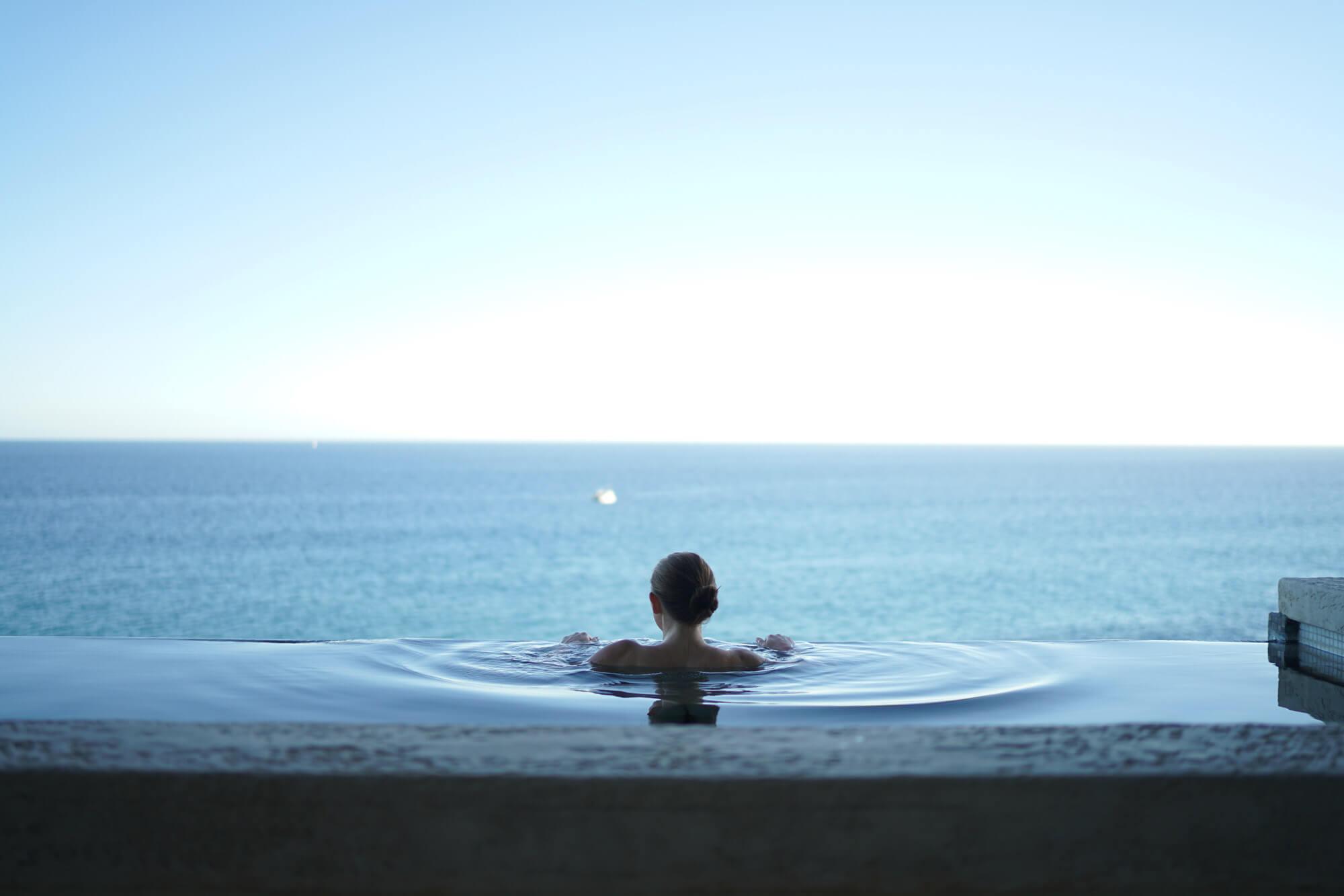 Jeune femme regardant la mer, en train de se baigner dans un hotel avec jacuzzi privatif