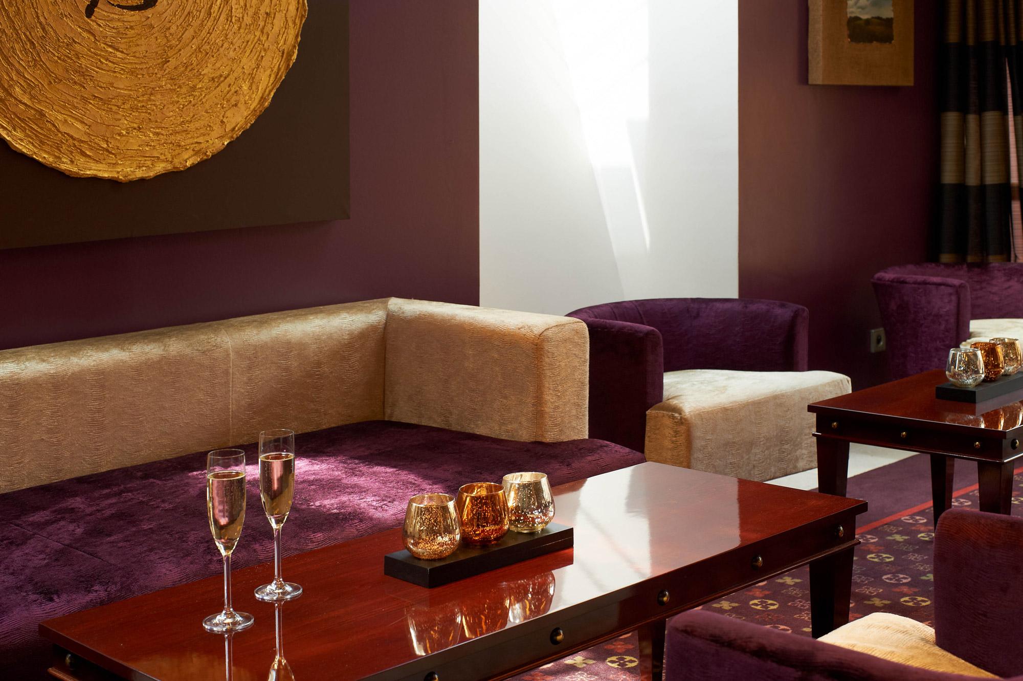 Verres de champagne posés sur une table basse dans un salon à l'Hostellerie des Châteaux & Spa