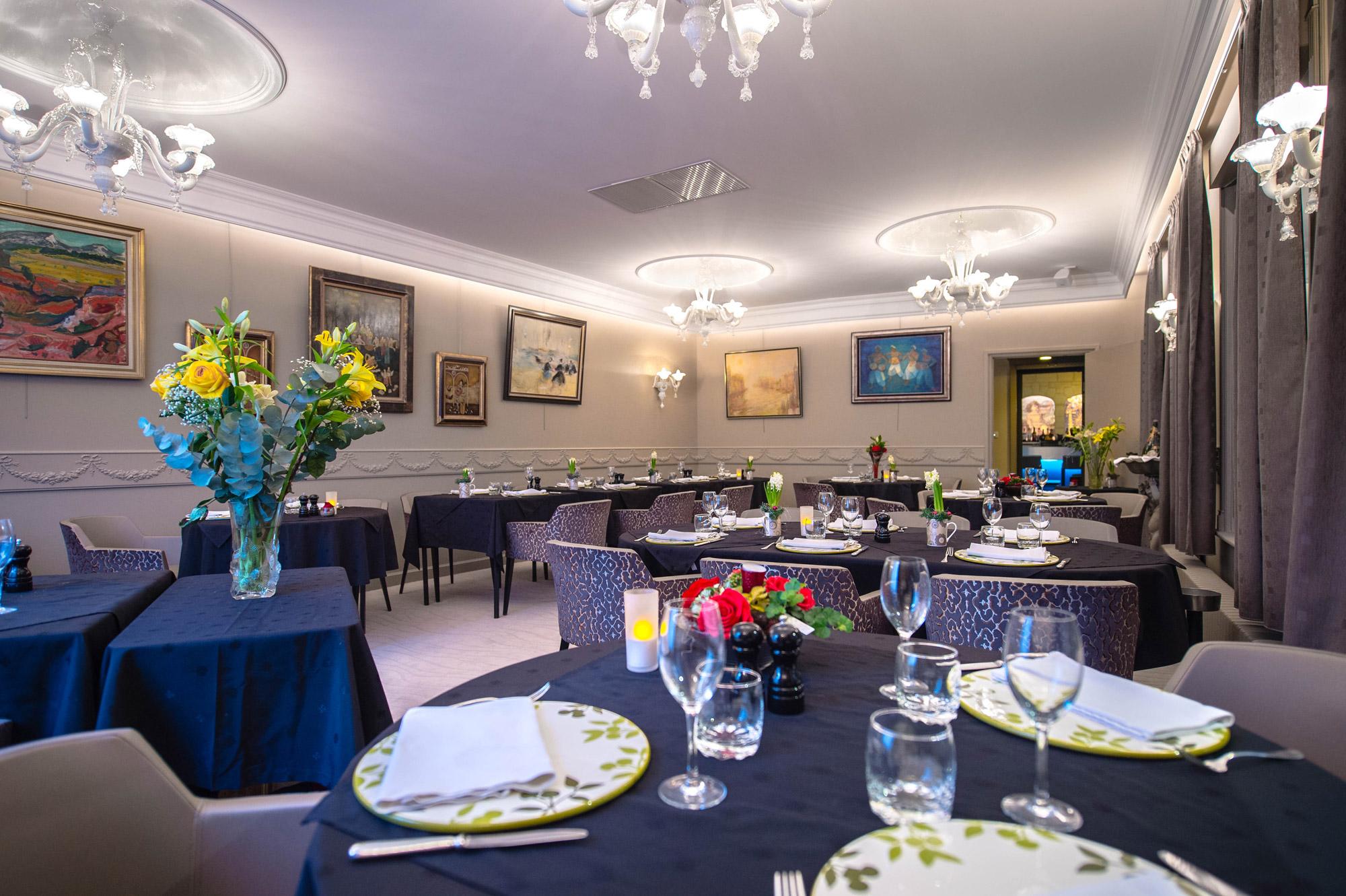 Salle de restaurant moderne et colorée avec tables dressées à l'hôtel La Terrasse à Douai