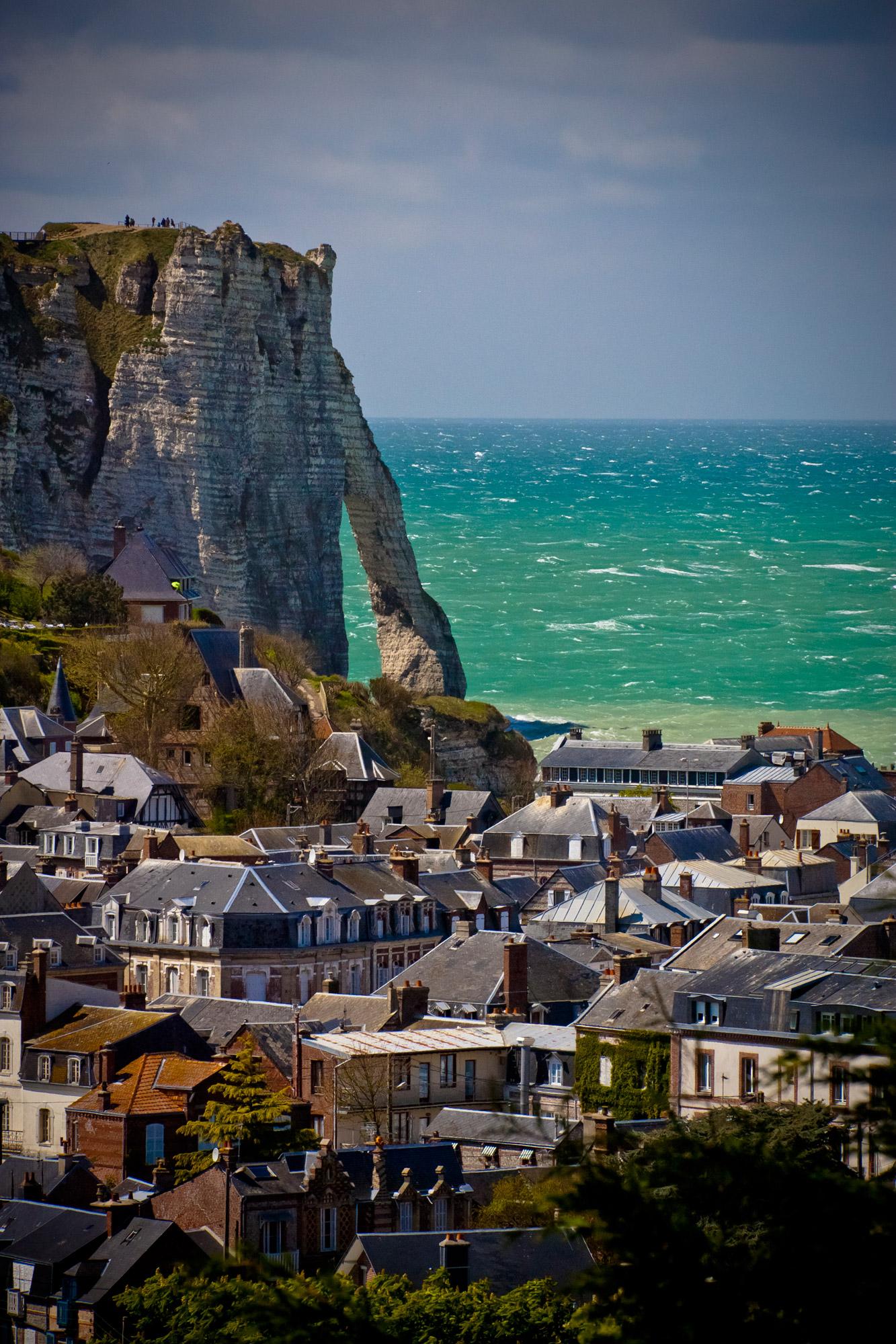 Toits des maisons de la ville d'Etretat et en arrière-plan une des falaises typiques surplombant la Manche