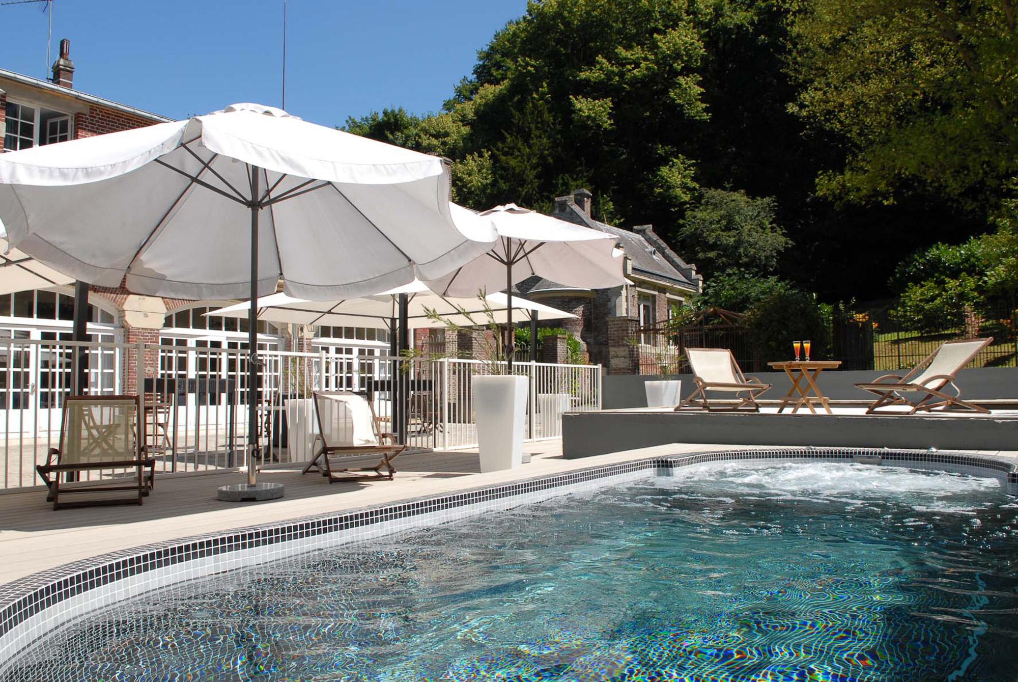 Piscine extérieure pendant l'été, avec transats et cocktails, au Domaine de Joinville & Spa en Normandie