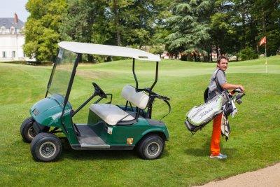 Joueur en train de porter son sac de golf près de sa voiturette