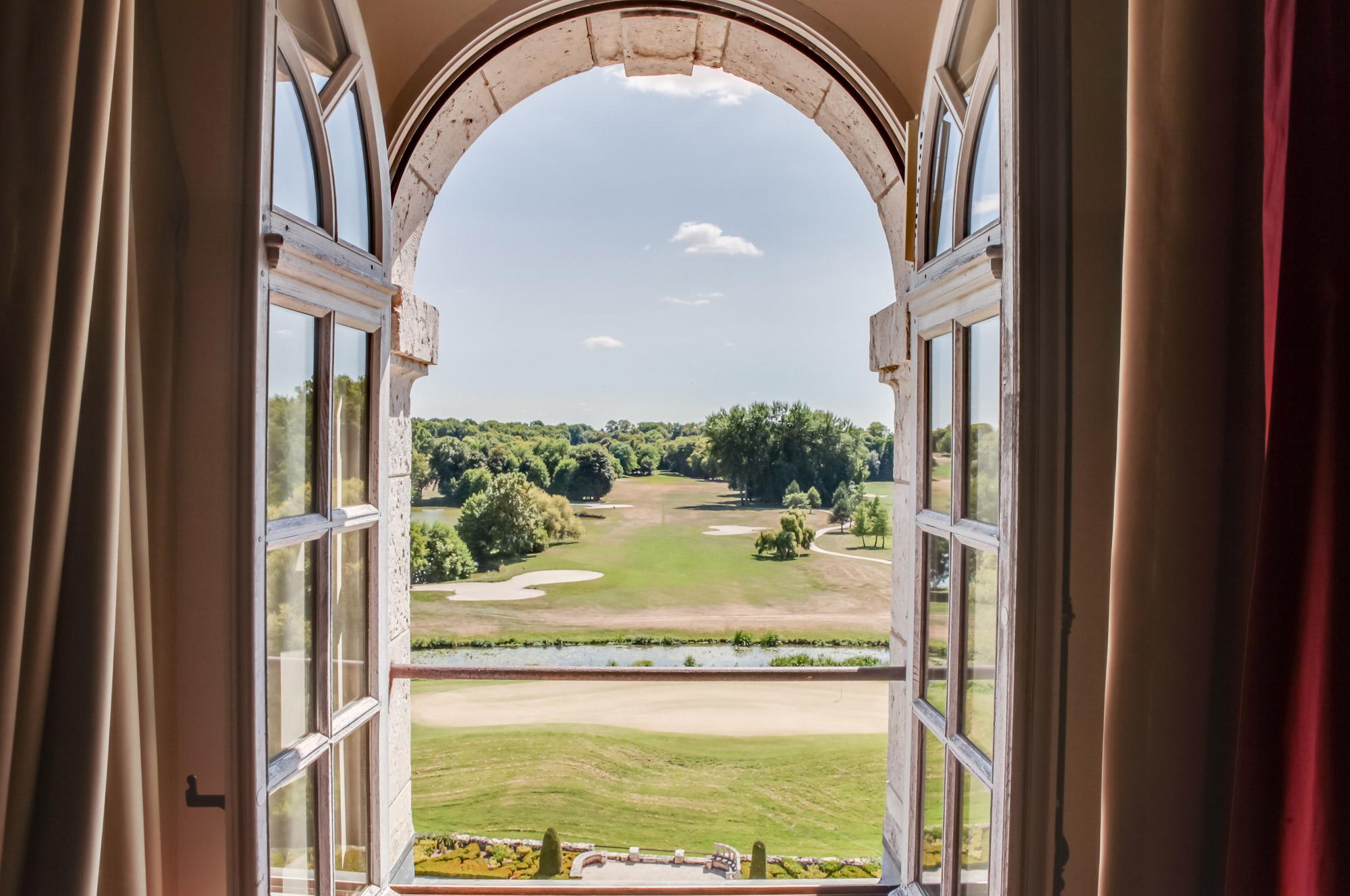 Fenêtre ouverte surplombant le parcours de golf de l'hôtel Château Golf & Spa d'Augerville idéal pour un séjour golf