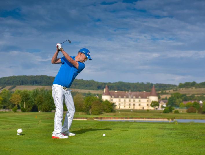 Joueur expérimenté amorçant son swing sur le green de l'Hôtel Golf du Château de Chailly en Bourgogne