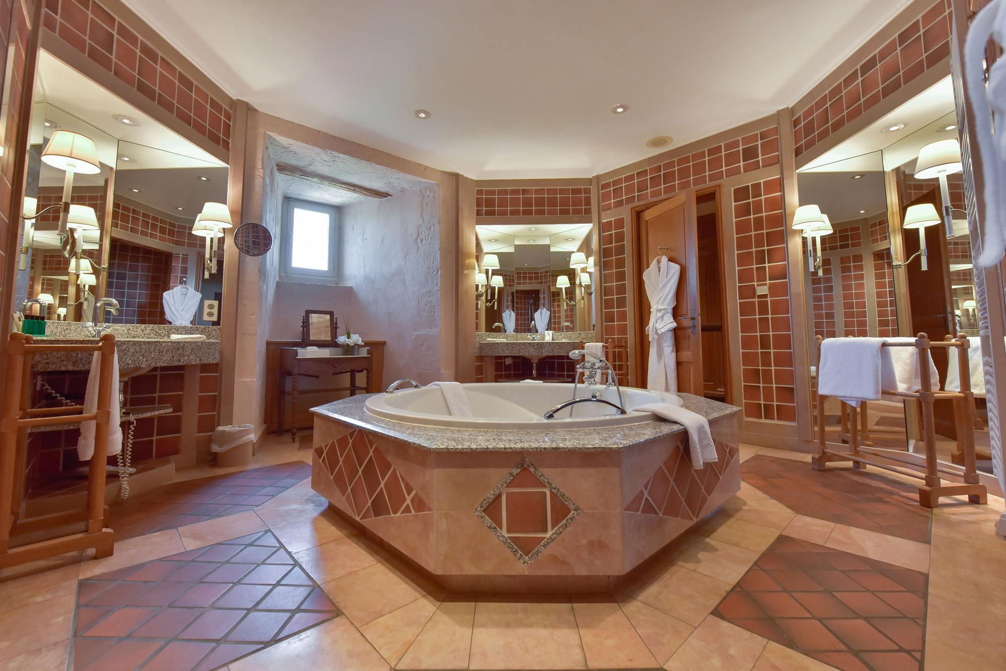 Salle de bains spacieuse avec vasque en marbre et baignoire centrale à l'Hôtel Golf Château de Chailly