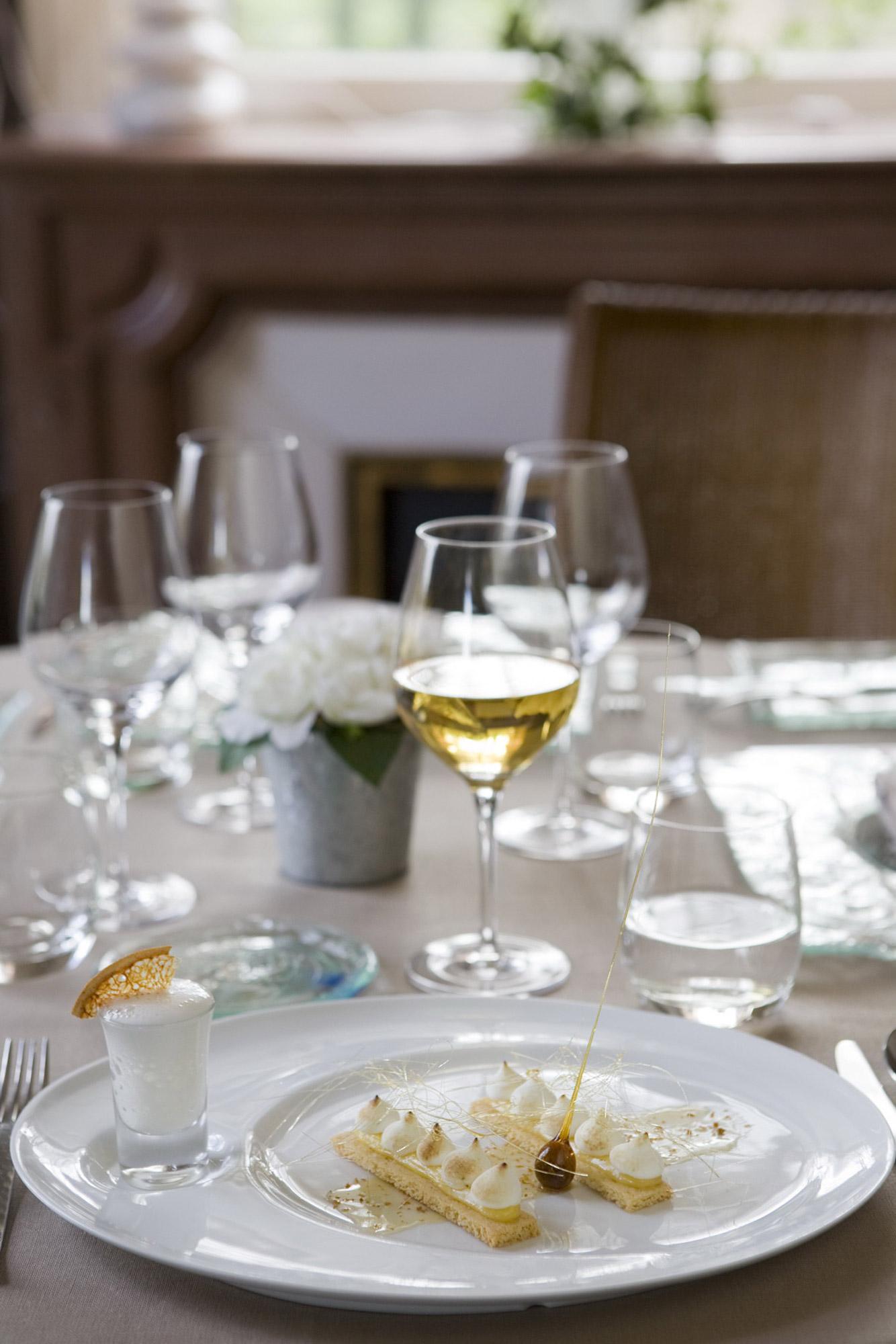 Table gastronomique dressée avec verre de vin blanc et dessert gourmand