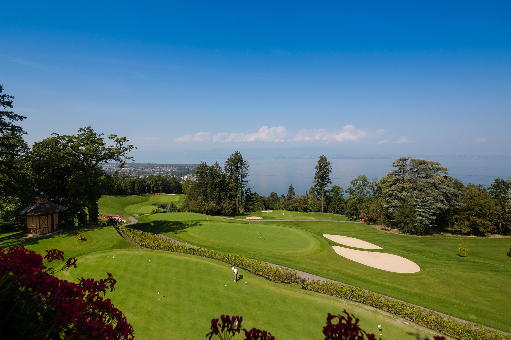 Joueur de golf sur le green bénéficiant de la vue sur le lac et sur les montagnes à Evian-les-Bains