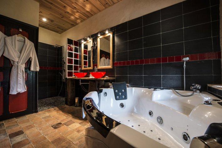 Salle de bains moderne avec 2 vasques rouges et une baignoire à remous au Château de l'Abbaye de Moreilles