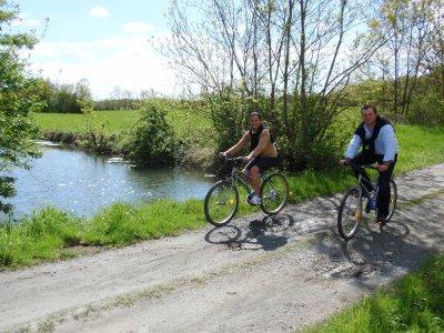 Jeune femme et jeune homme en train de se balader à vélos près d'un plan d'eau