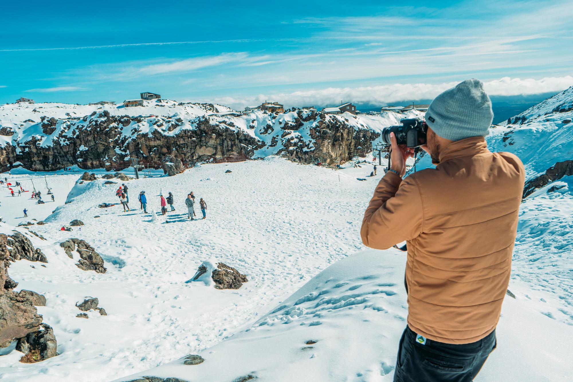 Homme en train de prendre une photo en hauteur, d'un groupe de randonneurs en pleine montagne enneigée par temps ensoleillé