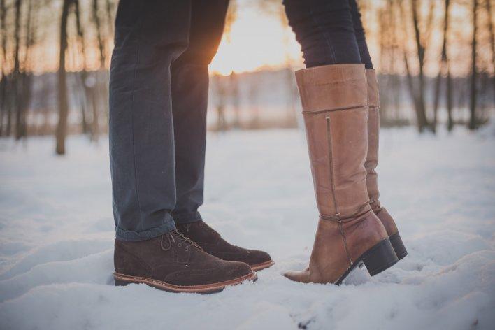 Gros plan sur chaussures homme et femme, suggérant une étreinte romantique dans la neige