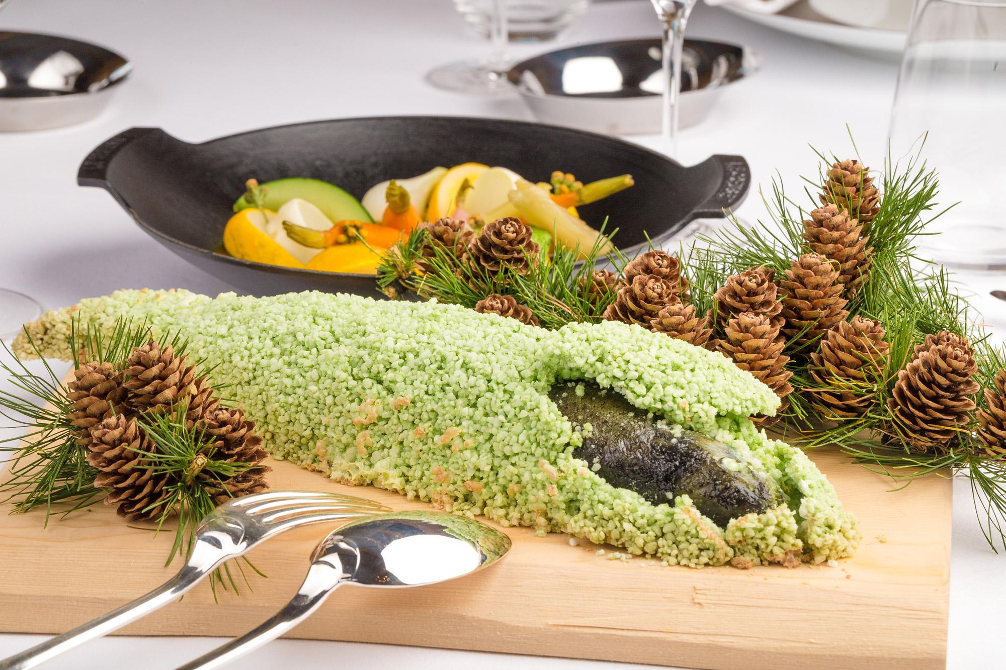 Planche de bois sur laquelle est servi un poisson en croûte décoré de pommes de pin