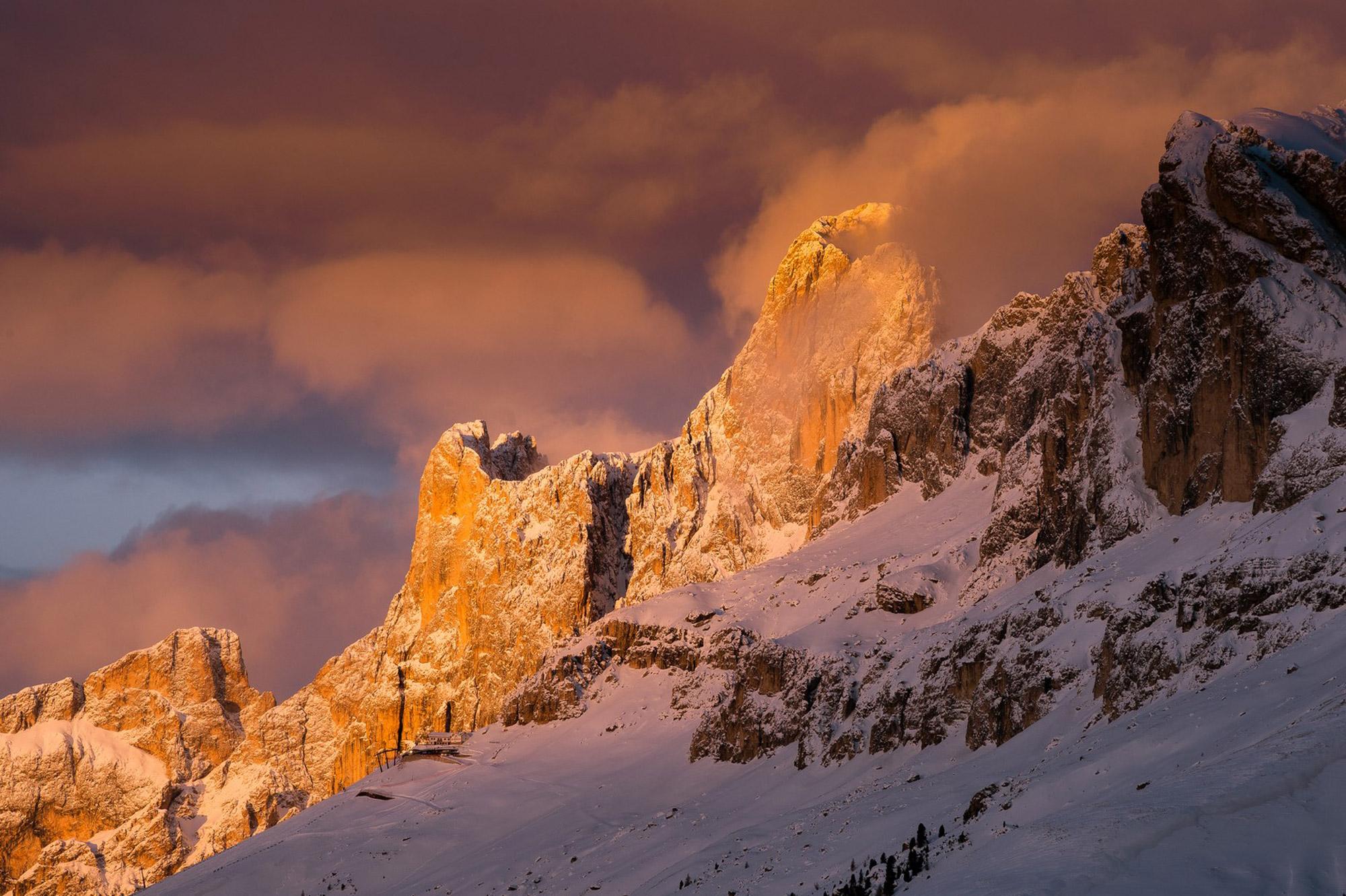 Paysage de montagne enneigé avec le soleil qui se couche sur le flanc gauche