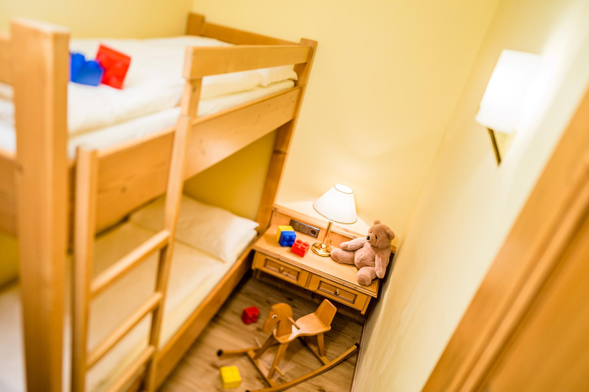 Chambre de type familial avec lit superposé et jouets d'enfants dispersés