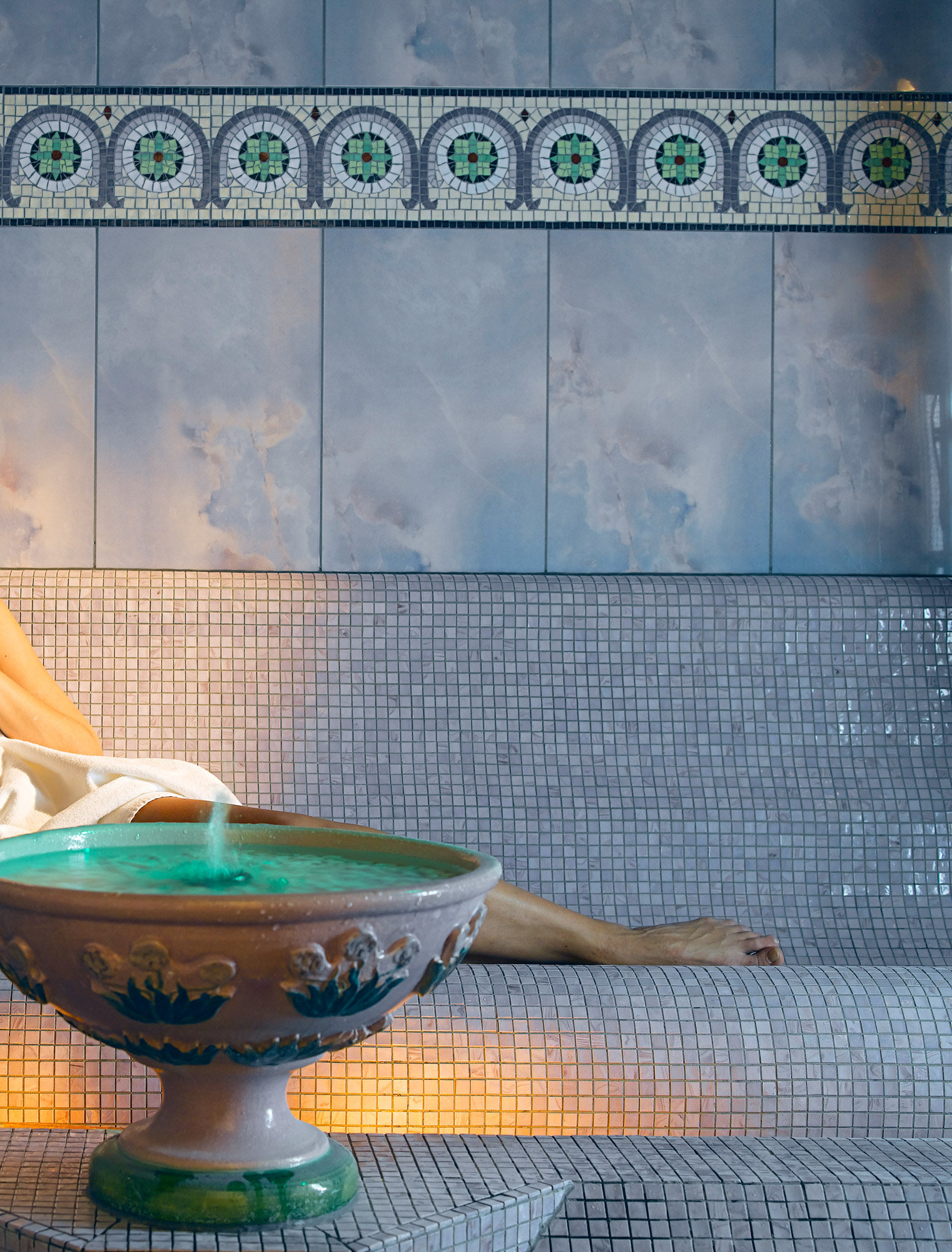Gros plan sur une fontaine placé dans un spa avec en arrière-plan une femme se reposant