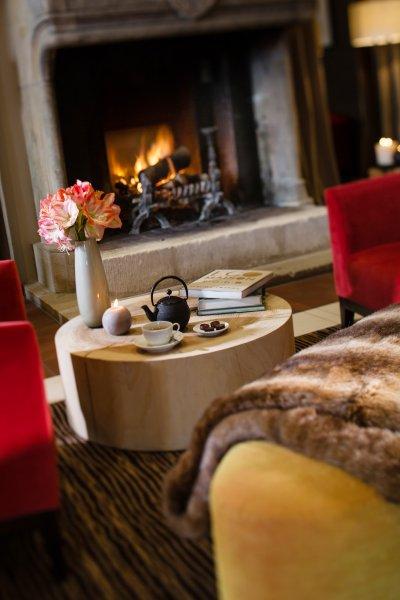 Salon avec fauteuils cosy, tasse de thé et feu de cheminée pour se réchauffer à la montagne