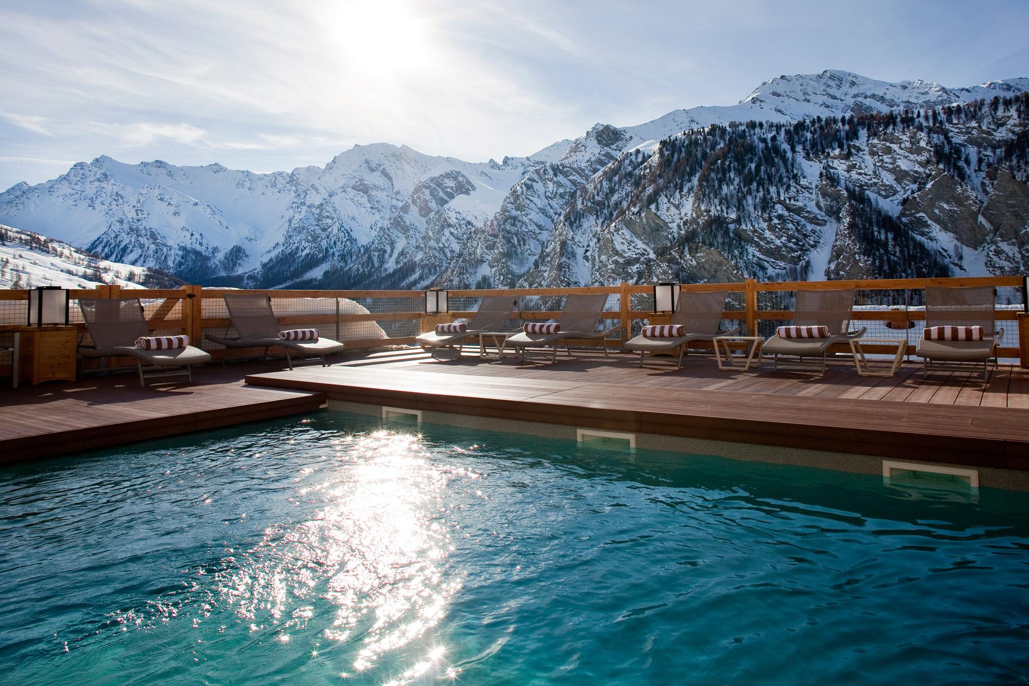 Piscine baignée par les rayons du soleil, avec vue splendide sur les montagnes enneigées