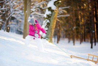 Petite fille habillée chaudement en blouson rose tirant une luge en bois sur la neige