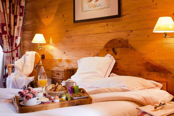 Petit-déjeuner copieux servi dans un plateau et posé sur un lit double d'une chambre de l'Hôtel Carlina près d'Annecy