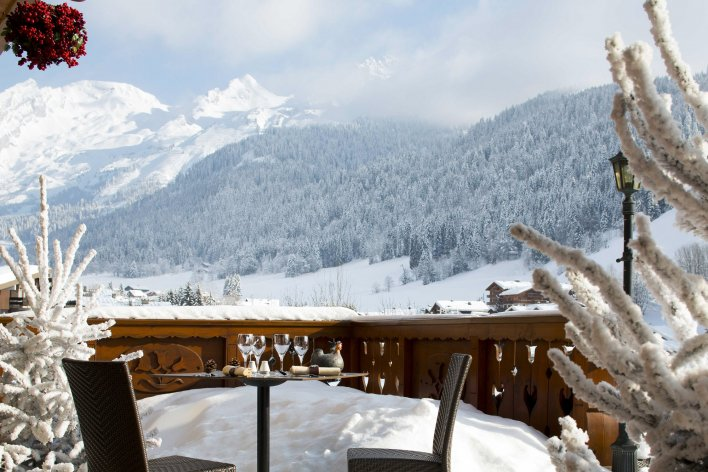 Table dressée en terrasse décorée de sapins, avec vue sur montagnes enneigées à La Clusaz