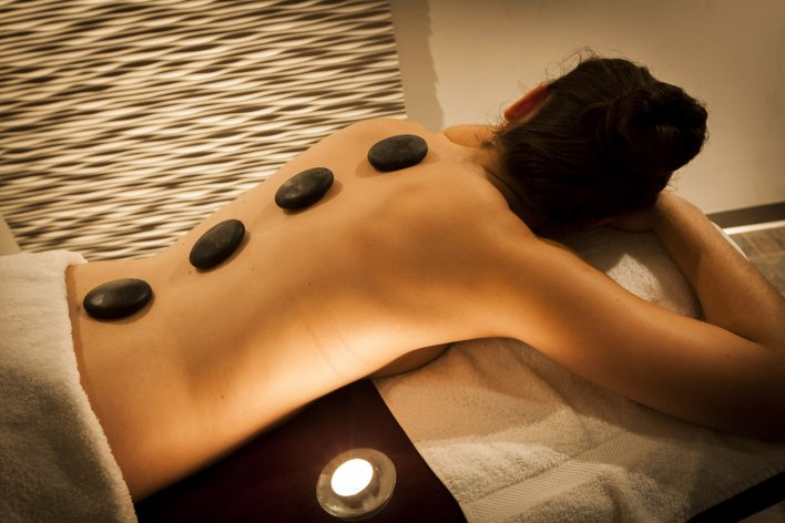 Jeune femme allongée sur le ventre, profitant des bienfaits d'un massage aux pierres chaudes