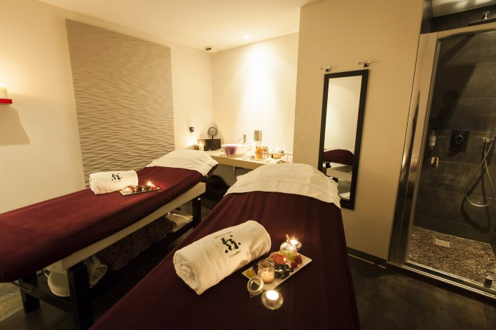 Salle comportant 2 tables de massage, avec plateau gourmand et cabine de douche