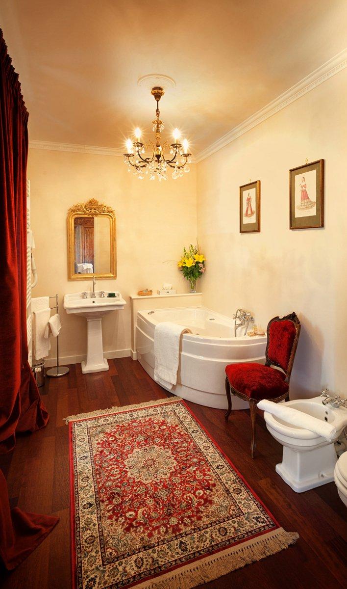 Salle de bain avec lavabo, baignoire et bidet sur parquet authentique recouvert d'un tapis persan