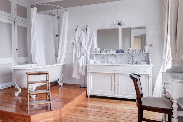 Salle de bain spacieuse, dans les tons blancs avec parquet clair au sol, comprenant une baignoire sur pied de style romantique.