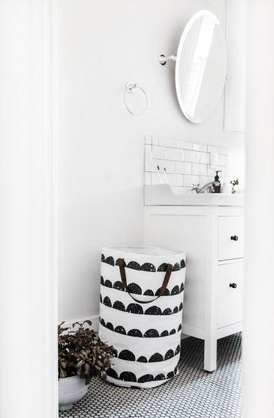 Meuble de salle de bain blanc avec carrelage mural, panier à linge noir et blanc et miroir mural