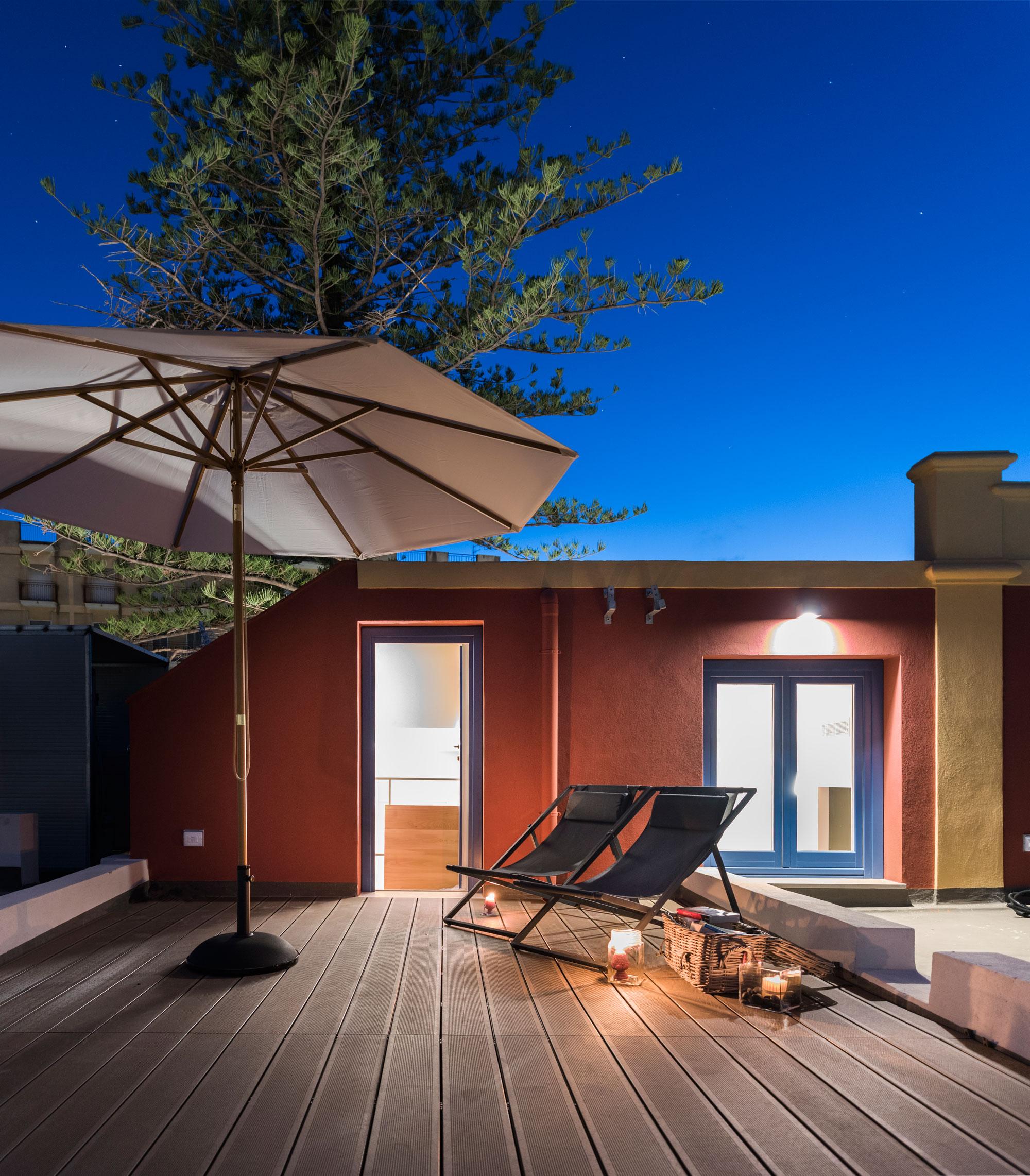 Terrasse en bois abritée d'un parasol sur laquelle sont posées 2 transats, vue de nuit