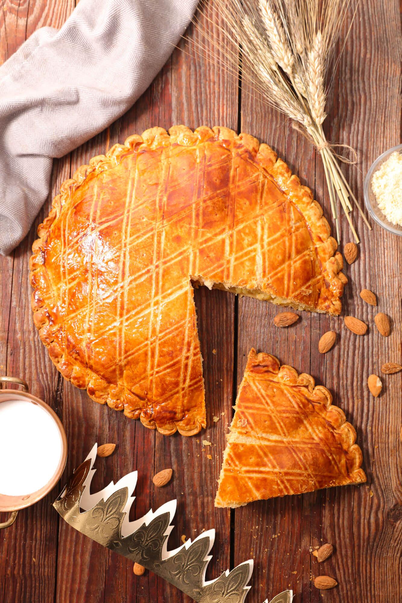 Gros plan sur une galette vue du dessus avec part découpée, amandes dispersées, épi de blé posés sur une table en bois