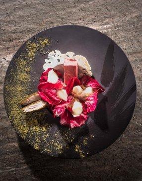 Assiette de couleur noire saupoudrée de poudre dorée contenant un plat gourmand réalisé par le chef du Piccolo Lago