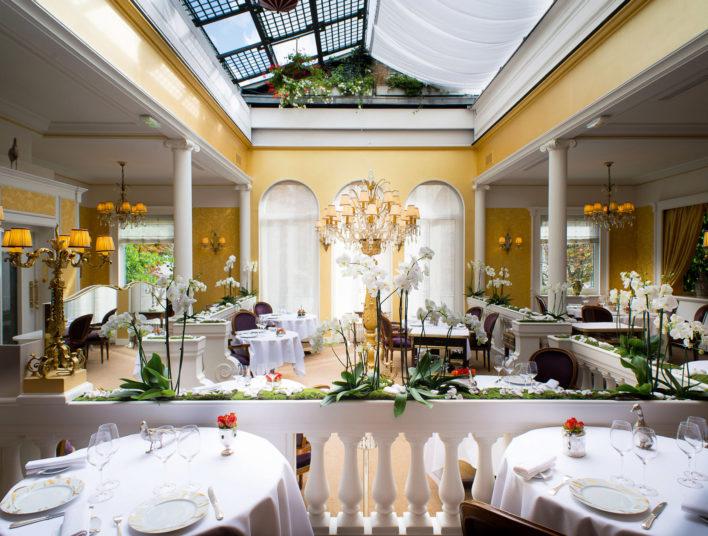Salle de restaurant avec tables dressées avec une verrière