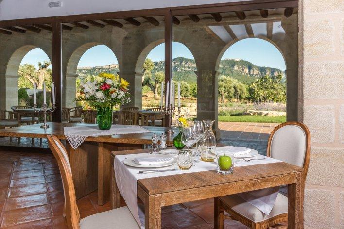 Gros plan sur une table dressée dans un lieu aux influences ibériques avec vue sur champs d'oliviers et montagnes