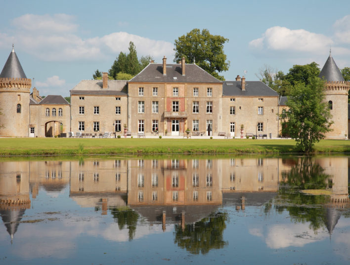 Façade typique d'un château médiéval traditionnel avec étendue de verdure et plan d'eau