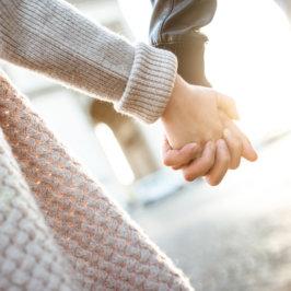 Gros plan sur une main féminine et une main masculine entrelacées