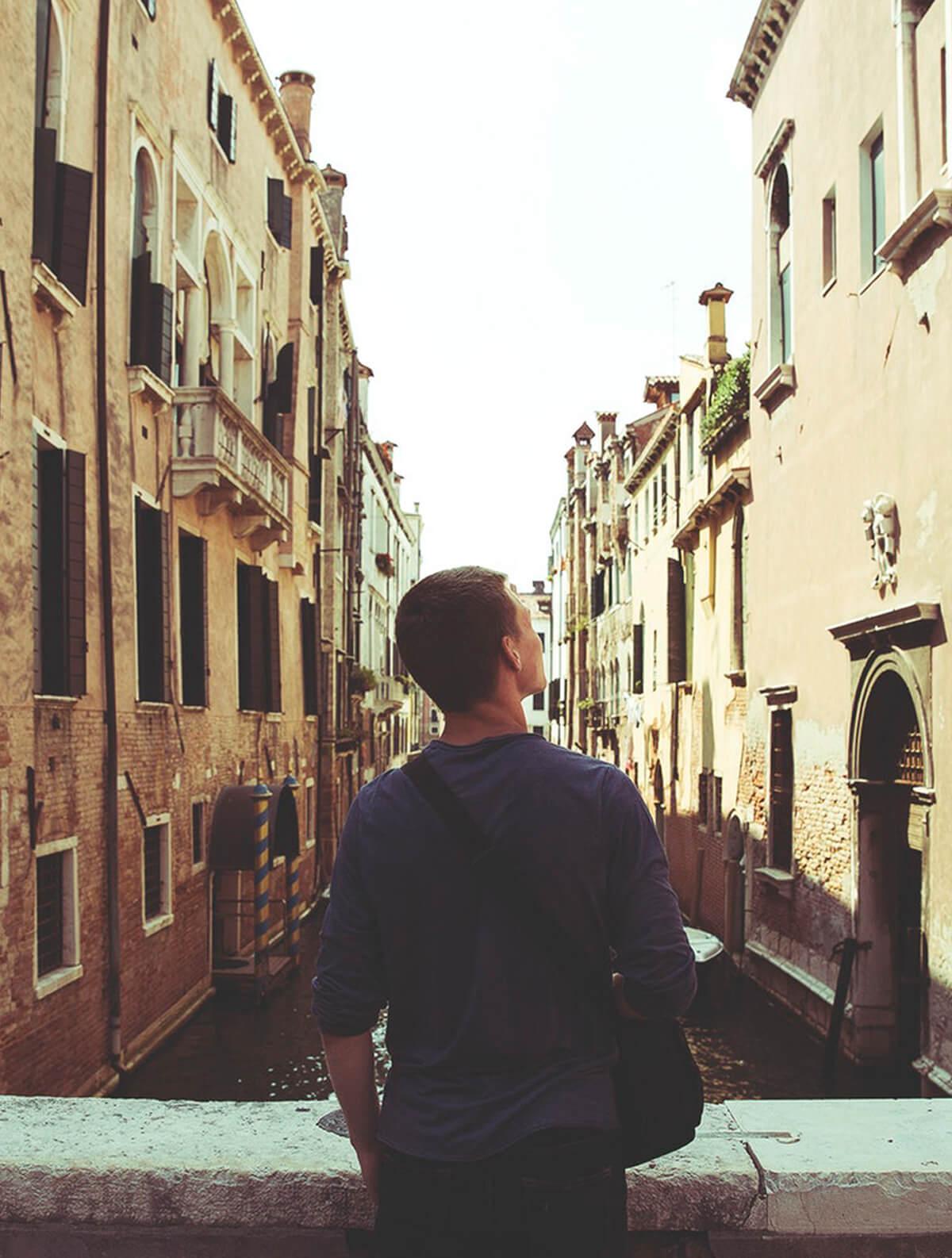 Jeune homme de dos dans la rue regardant des immeubles