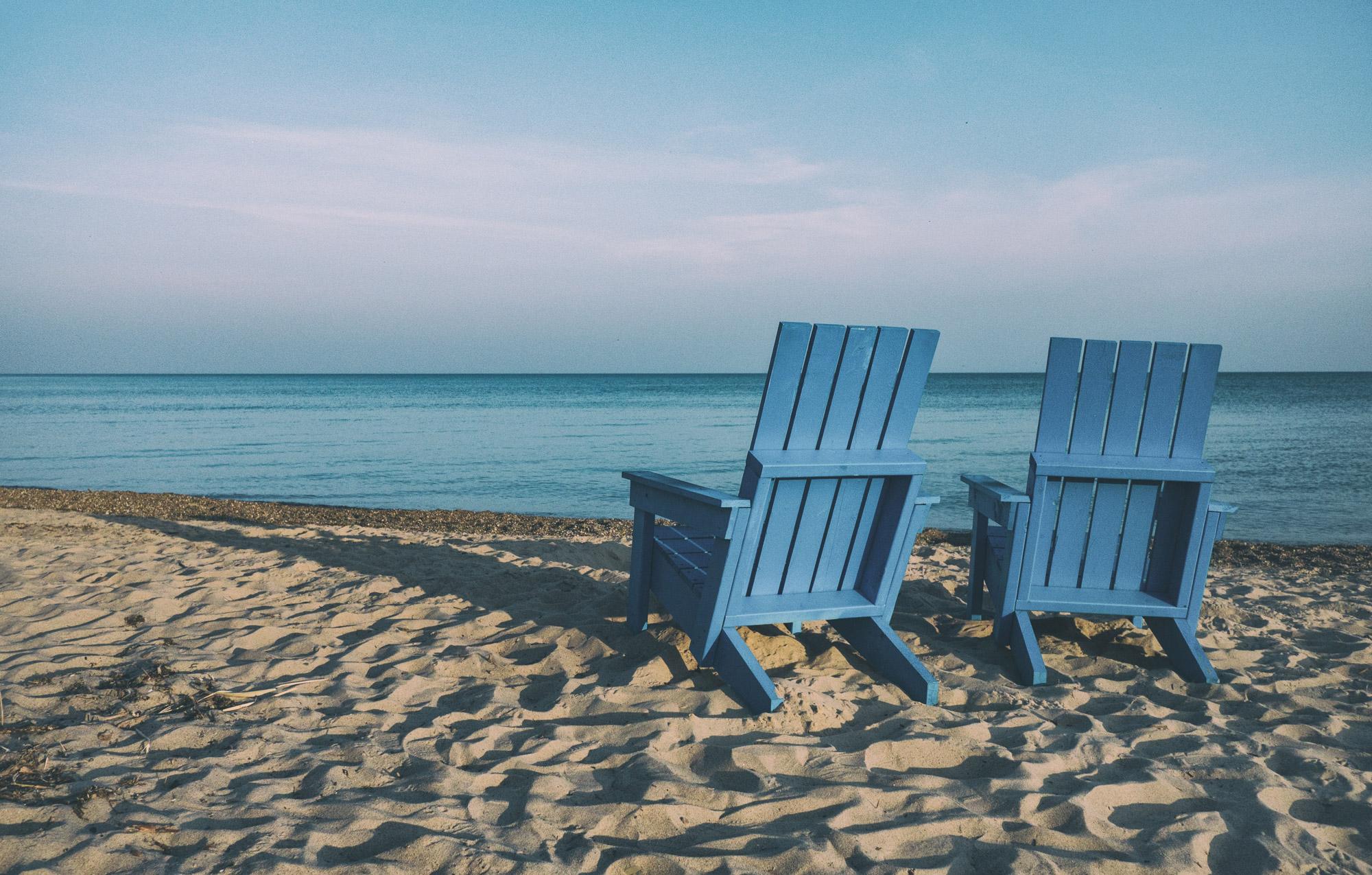 Deux fauteuils bleus en bois installés sur la plage et tournés vers l'océan